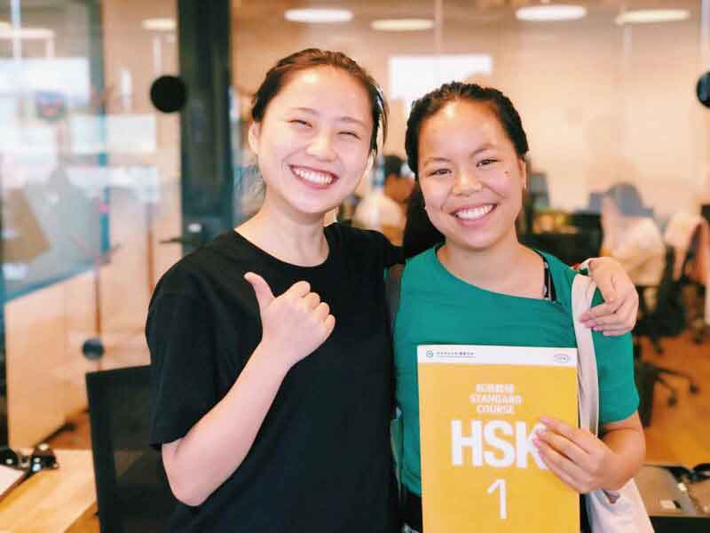 Teacher and student posing together with a HSK workbook