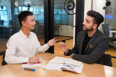 A teacher and student are learning mandarin by having a business conversation